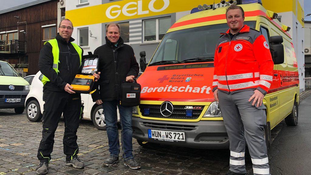 """Übergabe von zwei Defibrillatoren durch GELO Geschäftsführer Wolf-Christian Küspert an zwei engagierten """"Helfer vor Ort"""" des BRK."""